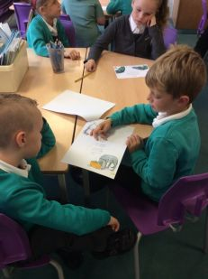 Jenson and Oliver discussing the rhyming words in their poem.
